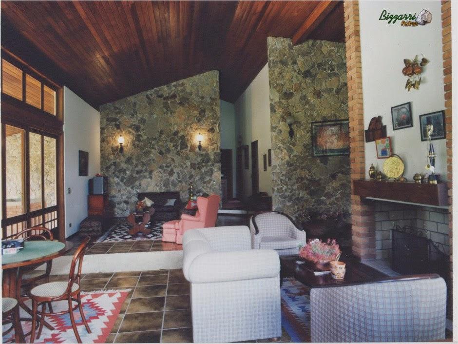 Na sala de estar da residência a parede com pedra moledo tipo chapada assentada com juntas bem encaixadas.