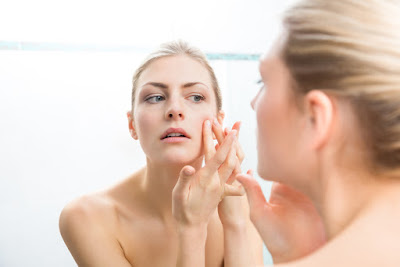 Young adult blond woman squeezing pimples on her face while looking at reflection in mirror