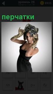 Женщина в черном платье одевает маску на лицо в длинных перчатках