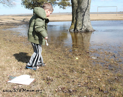 Boy collecting water sample to test pH in a STEM lab: STEMmom.org