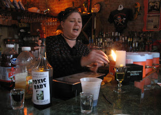 Bartender lighting up the sugarcube of an absinth drink, New Orleans