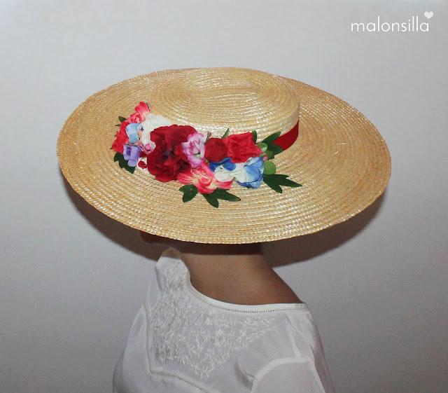 Chica posando de perfil con pamela de paja trenzada, flores y cinta en rojo y blusa blanca