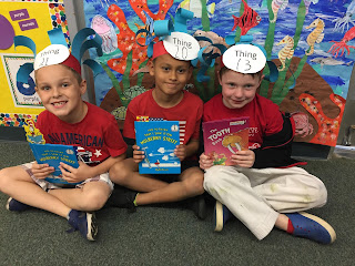 Three boys ready to read for Dr. Seuss Day