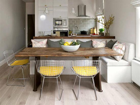 Phòng bếp kiểu dáng đẹp, hiện đại với gam màu trắng cùng những viên sàn gỗ màu xám và phòng ăn với bộ ghế làm từ những sợi dây kim loại kết hợp với nệm ngồi màu xám.