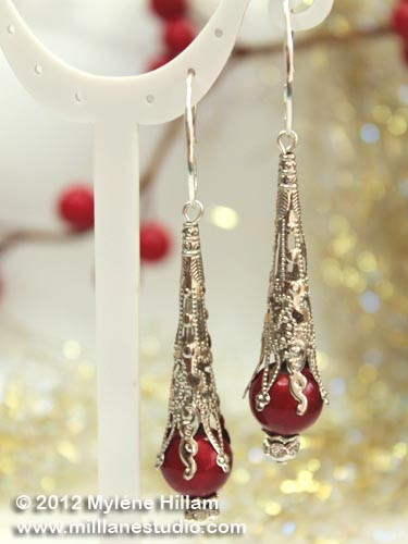 This striking pair of earrings combines a delicate looking filigree cone with a classic glass pearl - simple and elegant.