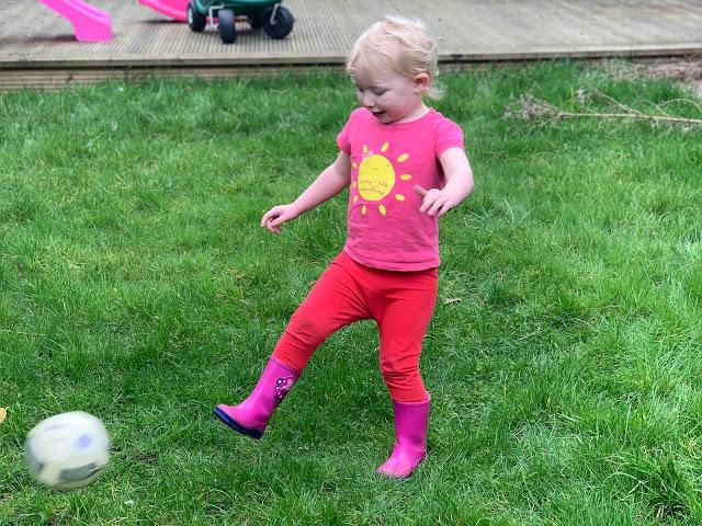 Toddler kicking a football on long grass