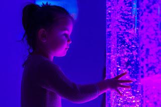Girl touches a purple bubble tube