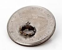 Meteliğe kurşun atarak delinmiş bozuk para