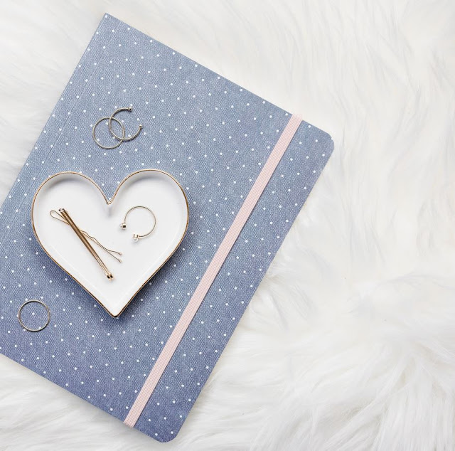 A denim flatlay with a notepad and a few sterling silver rings
