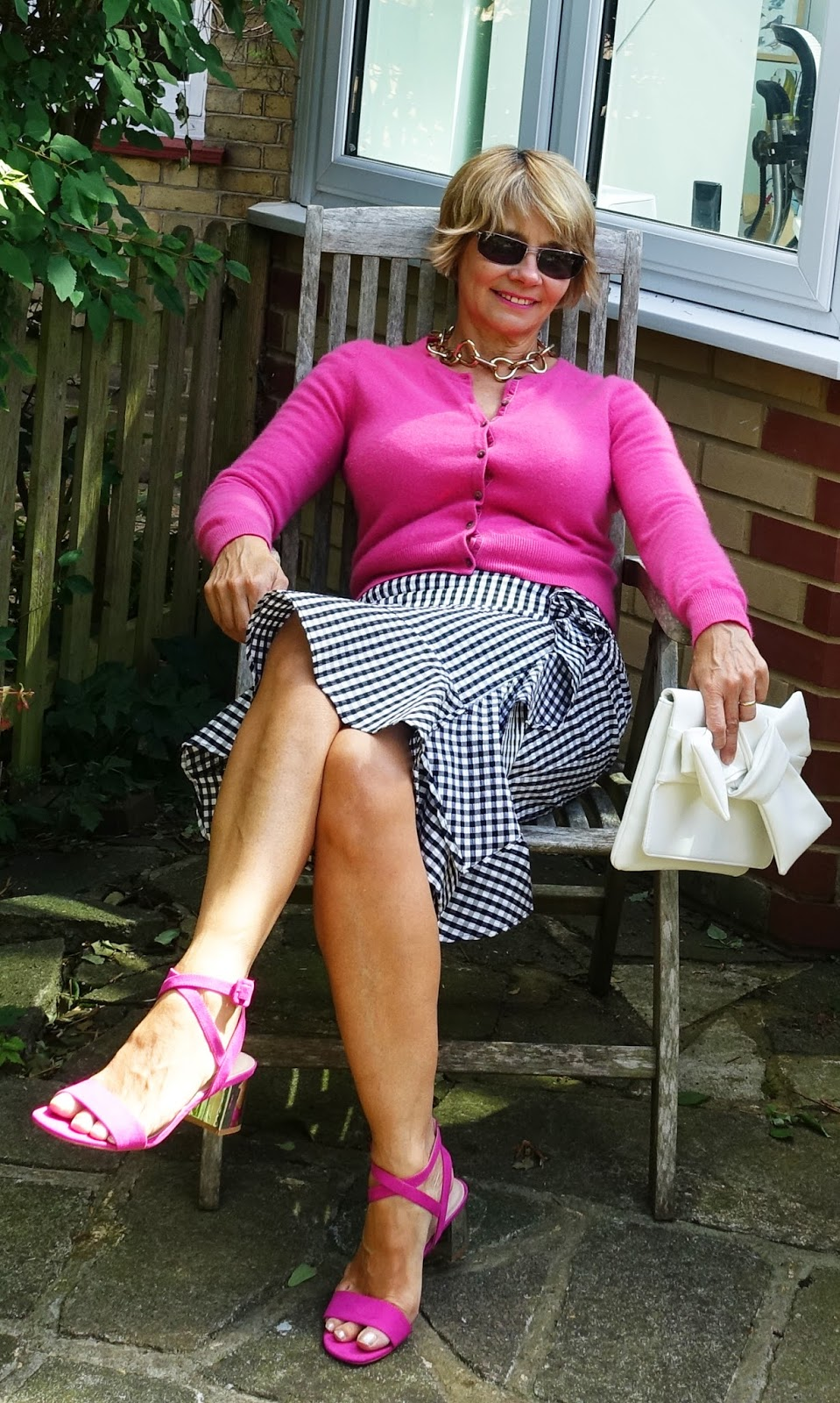 Styling a gingham skirt with a cashmere cardigan for cooler summer nights and with Converse trainers for a casual look