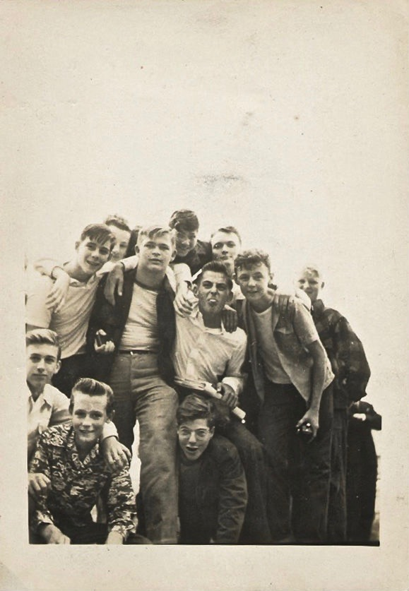 "Snapshot of teenage ""greasers"" in Brooklyn, New York 1950s. A group of boys mug for the camera. Boy in the center sticks his tongue out. The Con Stage of Development and other stories of parents and children. marchatron.com"