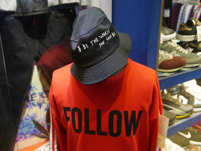"""Be The Worst You Can Be"" hat with ""Follow"" shirt on a mannequin at a shop in Jiangmen"