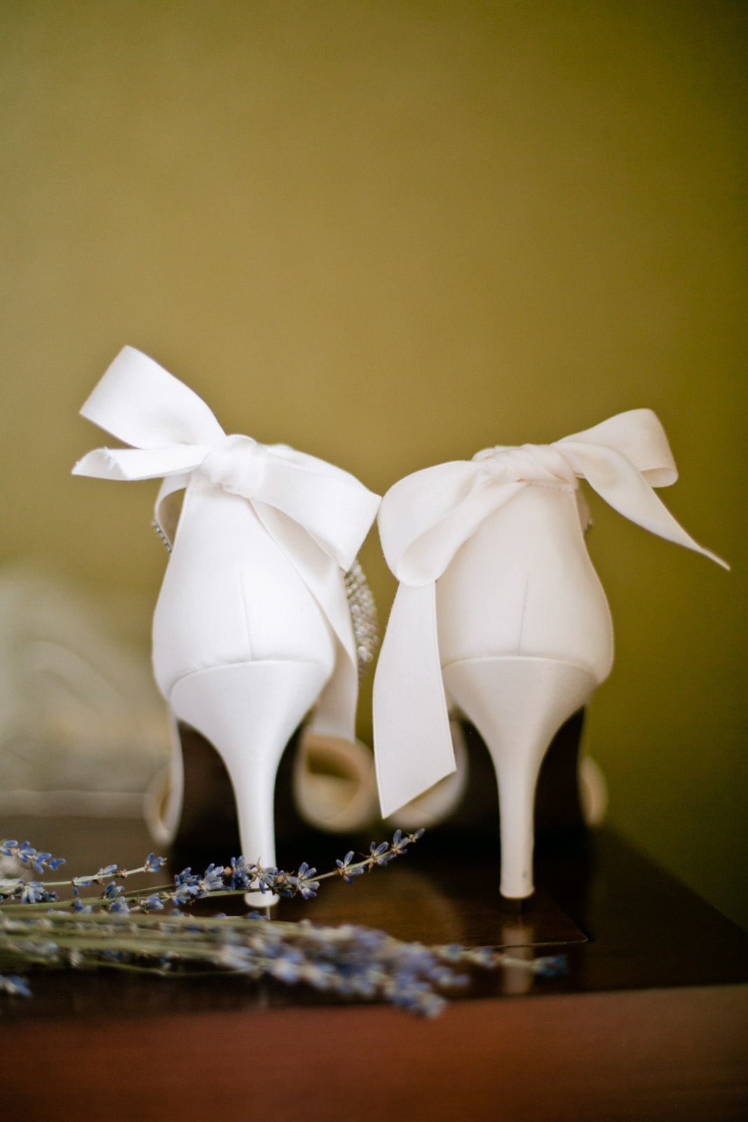 ivory bridal shoes complete with bows over the back of the shoe sit side by side. Design by Mina of New York
