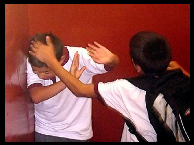 A male teenage bully attacks another male classmate