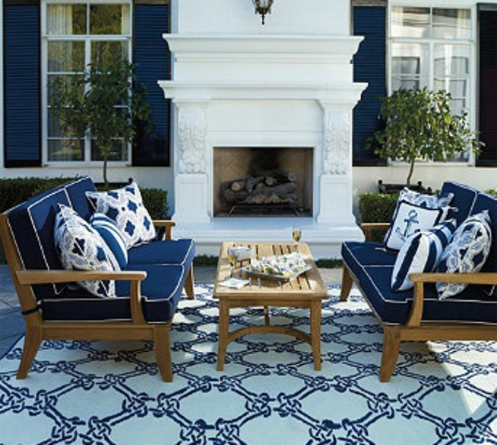 Coastal outdoor space with blue and white throw pillows