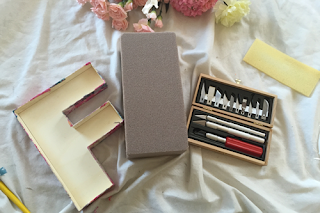 a wooden letter 'f' sits next to a fresh block of floral foam, and a wooden book full of craft knives and attachments