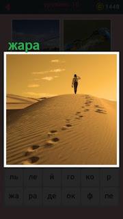 по пустыне в жару двигается человек, оставляя свои следы на песке