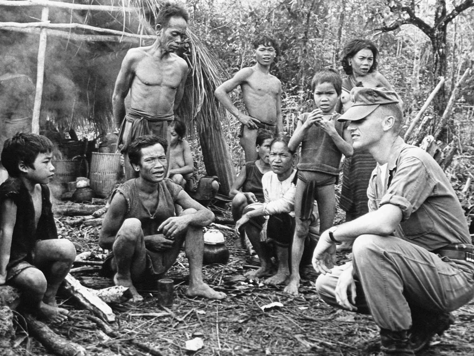 An American officer serving with the South Vietnam forces poses with group of Montagnards in front of one of their provisionary huts in a military camp in central Vietnam on November 17, 1962. They were brought in by government troops from a village where they were used as labor force by communist Viet Cong forces. The Montagnards, dark-skinned tribesmen numbering about 700,000, live in the highlands of central Vietnam. The government was trying to win their alliance in its war with the Viet Cong.