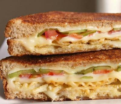 Sandwich panggang berisi tomat, asinan, keripik kentang, dan keju.