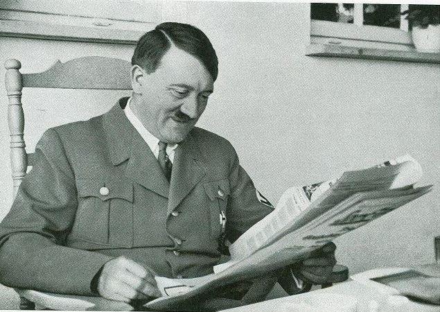 Adolf Hitler reading newspaper worldwartwodaily.filminspector.com