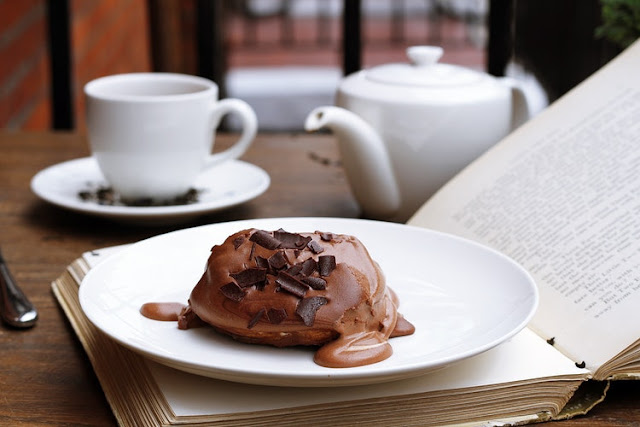 Chocolate cake on a plate along with a book and teacup and saucer