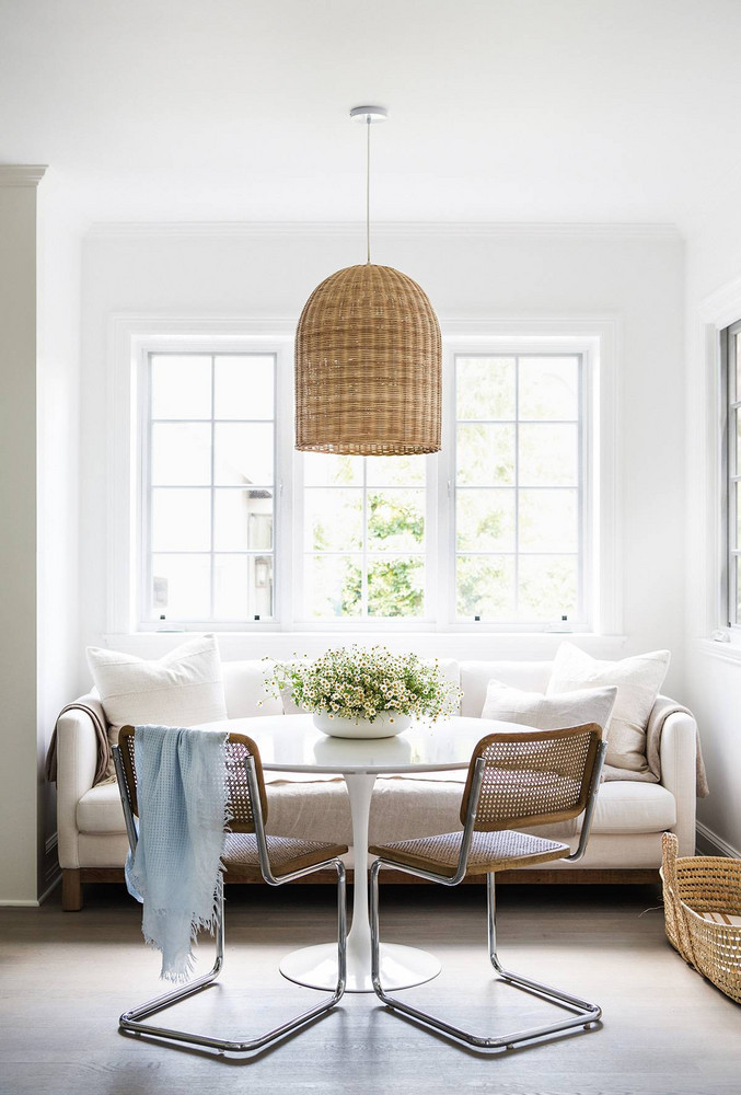All-white interior design and California farmhouse style in Erin Fetherston's home. Her kitchen's breakfast area has a comfy white sofa, Saarinen style tulip table, and simple Midcentury Breuer Cesca chairs with cane backs. #allwhite #kitchendecor #breakfastnook #bohochic