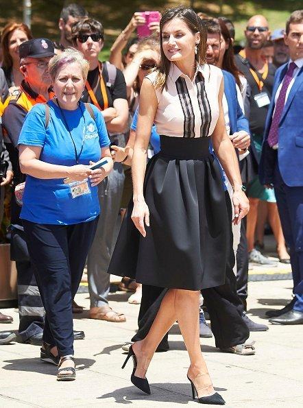 Queen Letizia wore Bogelund Jensen Fold Skirt, and Steve Madden Suede Pumps, and Coolook Hera Earrings, Letizia carried Carolina Herrera clutch