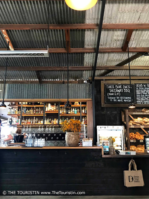 The tiled counter of a cafe under the ripple iron ceiling of a corrugated roof. Bottles and freshly baked bread on shelves in the background.