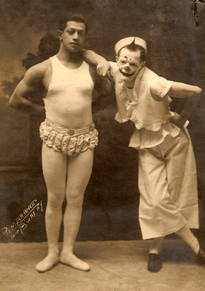 image of a promotional image for my great-grandfather's act; he is pictured next to a dark-skinned man in an acrobat's costume; my grand-father is wearing clown make-up and a clown costume