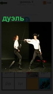 На сцене в театре двое актеров играют сцену дуэль. В шляпах и шпаги в руках
