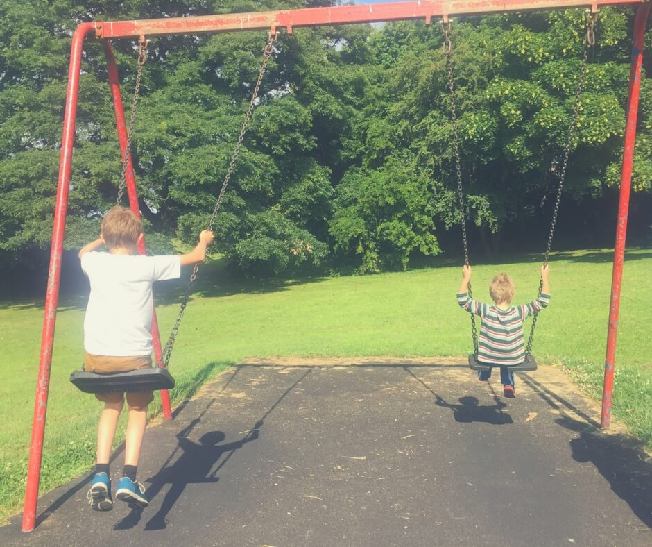 Two boys enjoying the swings in the sun.