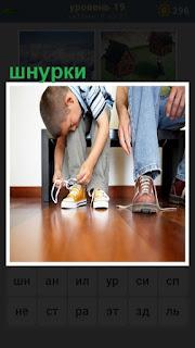 мальчик наклонился и завязывает шнурки на ботинках