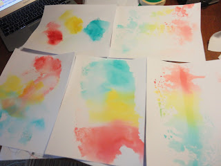 Five sheets of card with messy ink patterns in red, yellow and blue