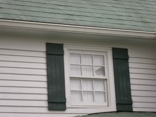 Tin roof repair with green acrylic has aged in appearance
