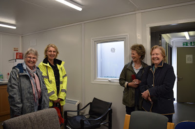 Four ladies stand in a portacabin