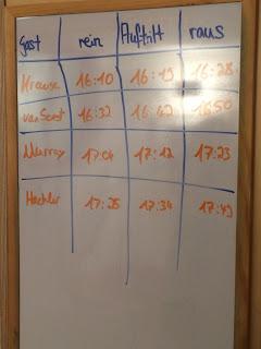 Eine weiße Tafel, auf der Handschriftlich in einer Tabelle notiert ist, wann welcher Gast ins Studio muss