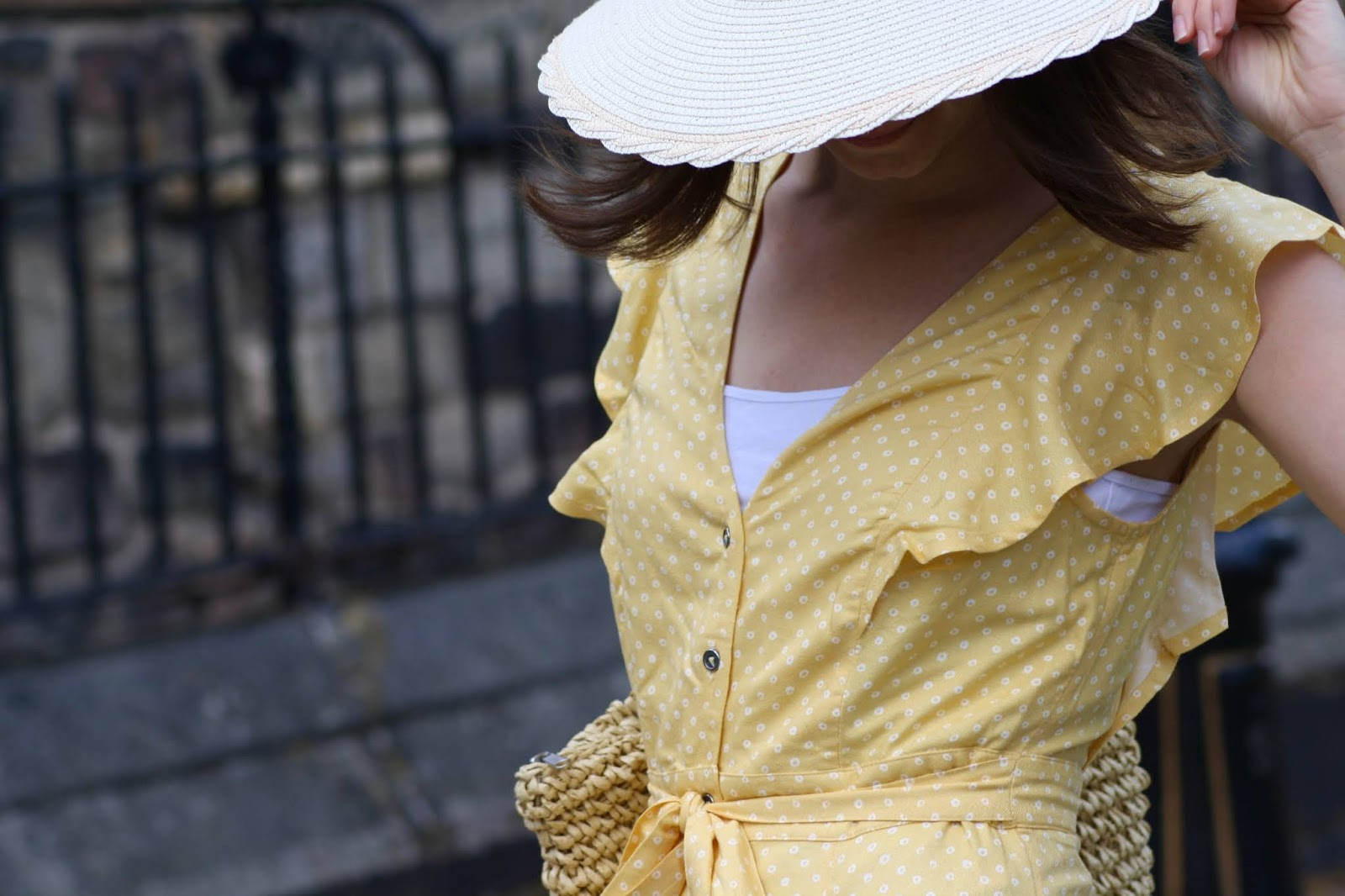 Abbey, wearing a yellow midi dress and straw hat, stands with her head down so that the brim of her hat can be seen