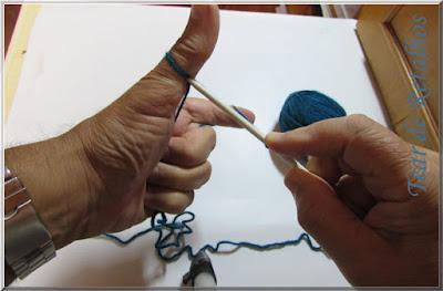 Foto mostrando o local em que deverá ser colocada a agulha sob o polegar para pegar o laço no início da execução de um ponto da montagem à italiana.