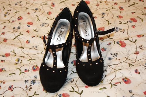 black t-bar studded court shoes from new look sitting on an IKEA beadspread duvet, unbuckled, from the front