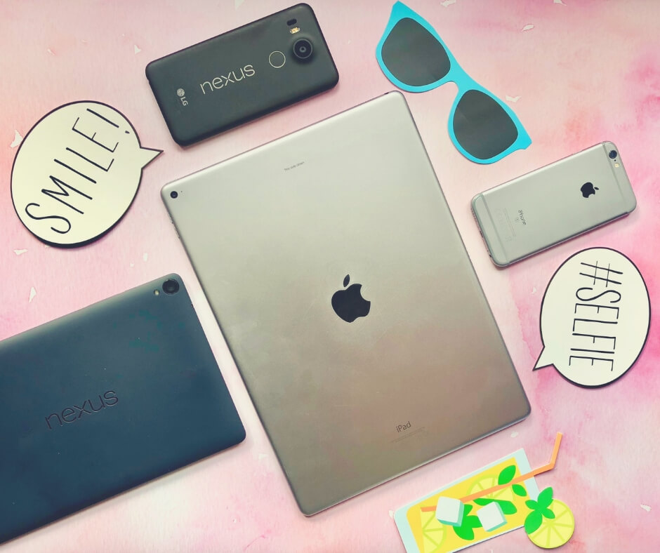 iPad, nexus devices, laid on a table with picture of sunglasses and a drink nearby.