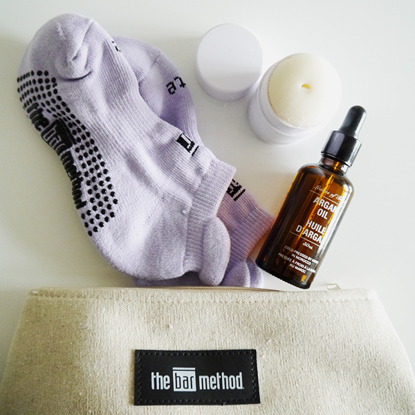 Flat lay featuring makeup and toiletries bag and lilac grippy socks from the Bar Method, Agent Nateur natural deodorant, Leaves of Trees argan oil