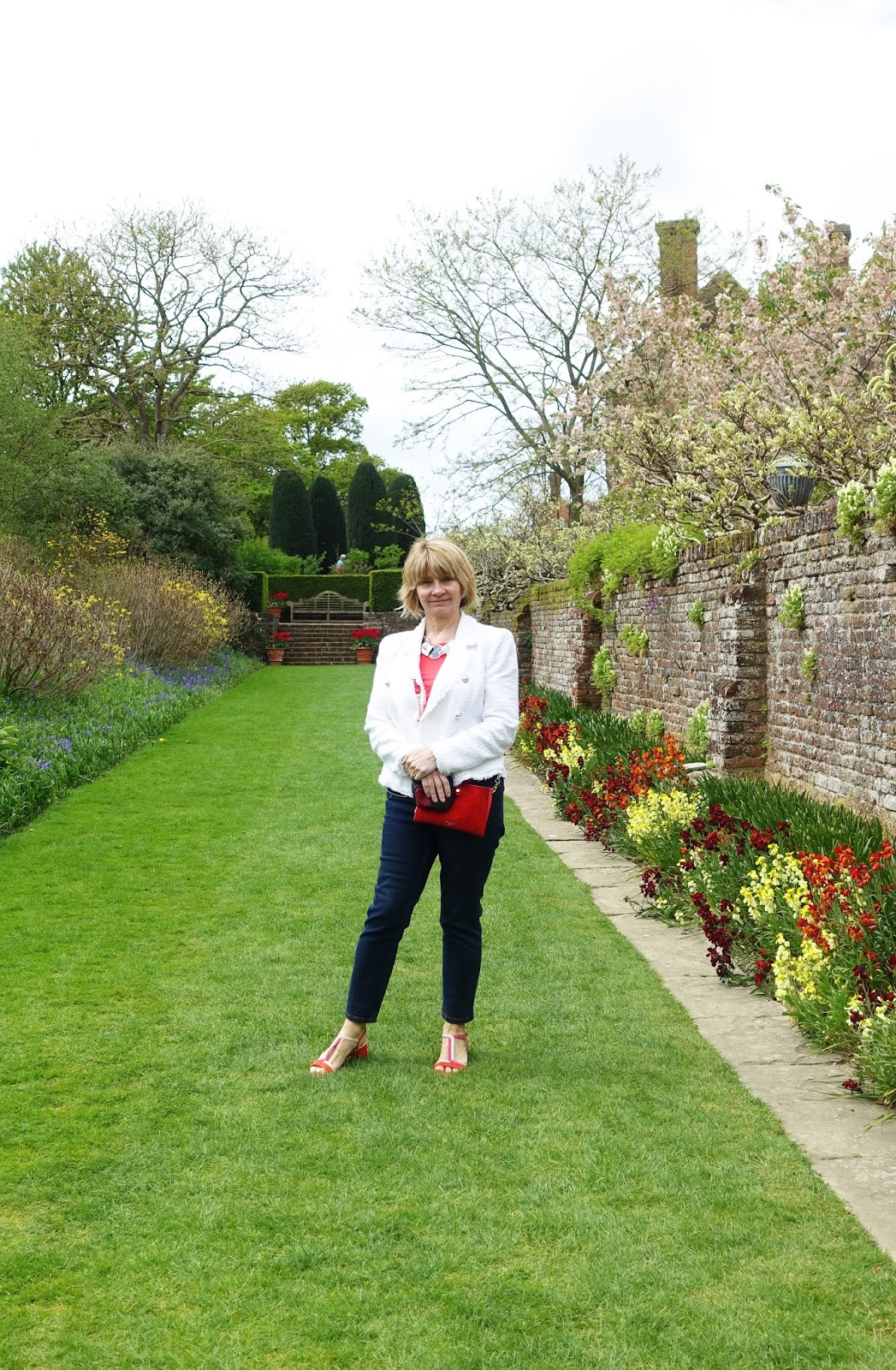 Over 50s blogger Gail Hanlon in red and white with blue jeans in Sissinghurst Gardens