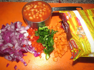 baked beans and chopped vegetables with packs of noodles