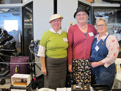 Three women dressed in 1940s outfits behind a stall at a miniatures convention.