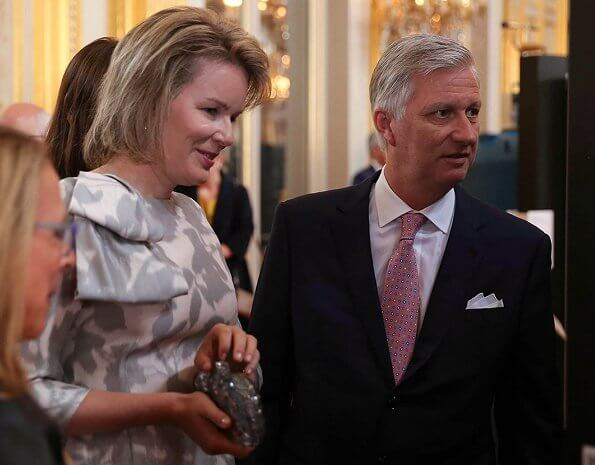 Queen Mathilde Natan blouse from Natan Graphics Couture and carries Diane von Furstenberg silver clutch