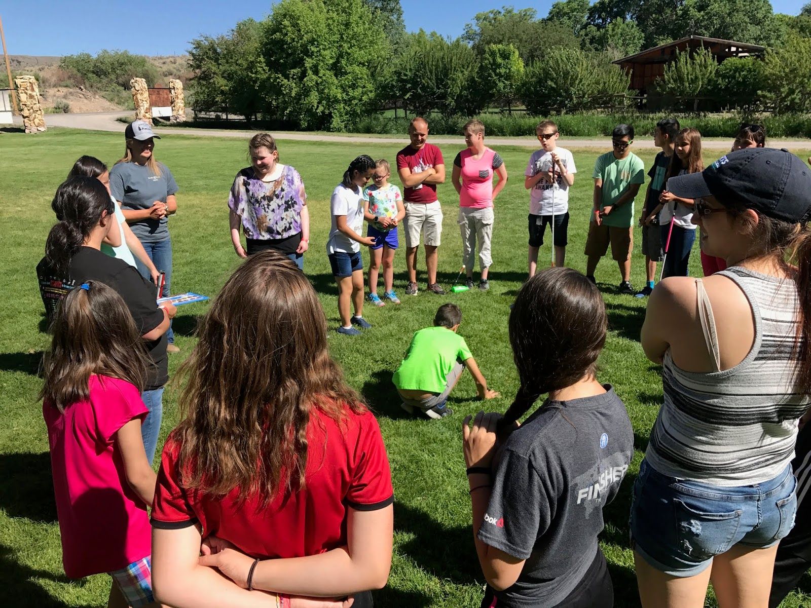 Students are in a circle for lawn games playing a game.