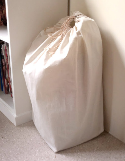 A calico drawstring bag in the corner next to the bookcase. The neutral colour blends in to the decor and hides a mini bale of oaten hay.  There is a circular opening at the top. It is drawn closed by a home-made twisted cord.