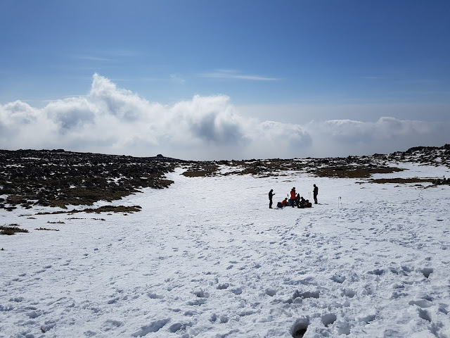 A group of hikers resting off the trail on the top of snow. You can see the field dropping off and the clouds hanging on par beyond.