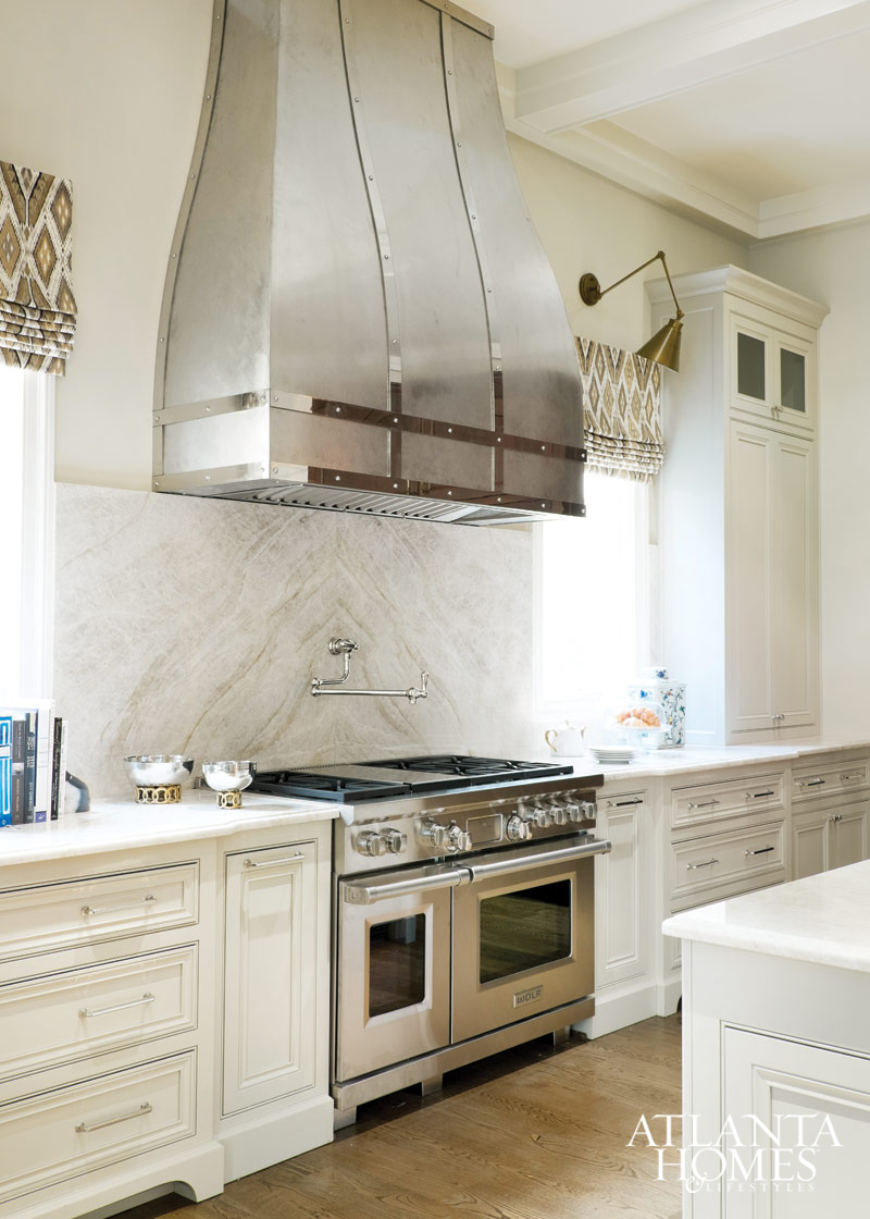 Stunning white kitchen with marble slab backsplash and modern lighting