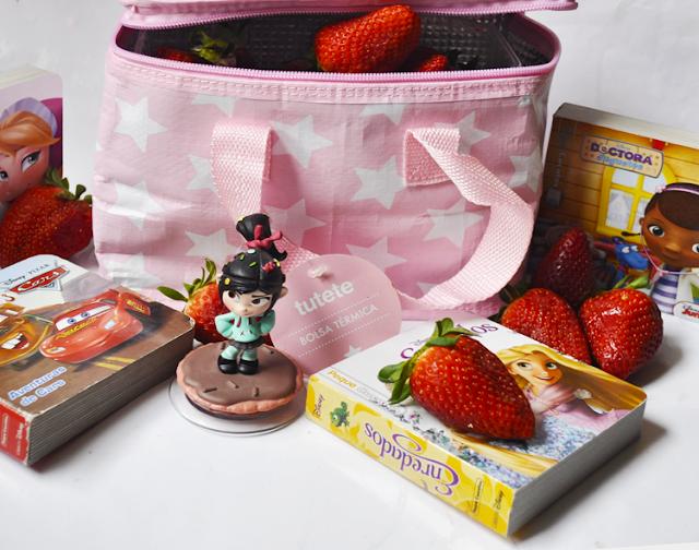 libros diseny y fresas rodean una bolsa rosa de tutete llena de fresas
